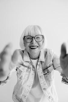 Portrait d'une femme élégante aux cheveux gris et en veste en jean vous étreignant ou faisant un selfie