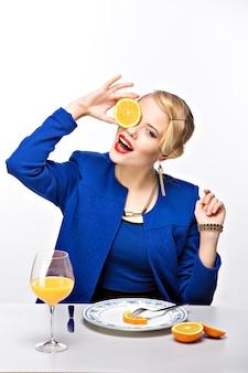 Portrait de femme élégante blonde tenant coupe orange près des yeux
