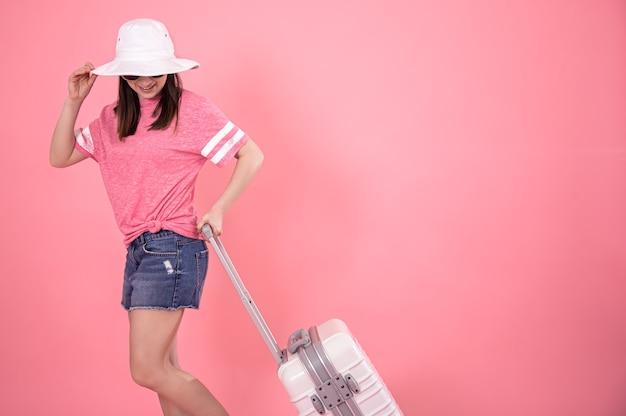Portrait d'une femme élégante sur fond rose avec une valise pour voyager.