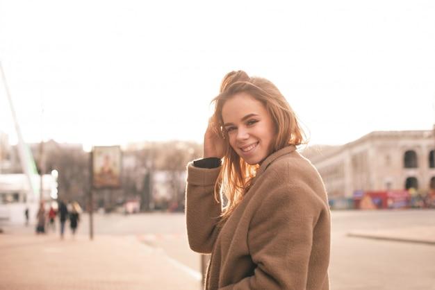 Portrait d'une femme élégante sur le fond de la rue au coucher du soleil, regardant dans la caméra, souriant et fixant ses cheveux