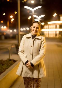 Portrait de femme élégante heureuse posant dans la rue la nuit