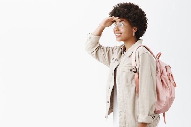 Portrait de femme élégante à la peau sombre créative et émotive avec une coiffure afro, tournant à gauche et regardant au loin avec la main sur le front, posant avec sac à dos
