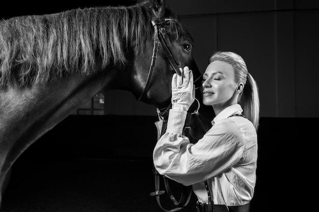 Portrait d'une femme élégante serrant un cheval pur-sang. concept d'amour et de soins. technique mixte