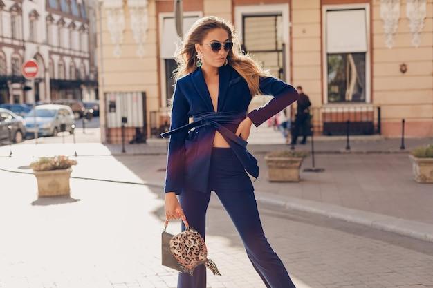 Portrait de femme élégante sexy marchant dans la rue en costume bleu portant des lunettes de soleil sur la journée d'été ensoleillée