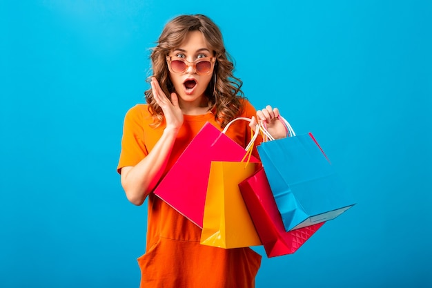 Portrait de femme élégante souriante séduisante excitée accro du shopping en robe à la mode orange tenant des sacs sur fond bleu studio isolé