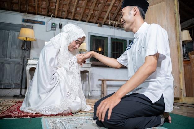 Portrait de femme embrassant la main de son mari après avoir prié ensemble à la maison. sholat ou salat