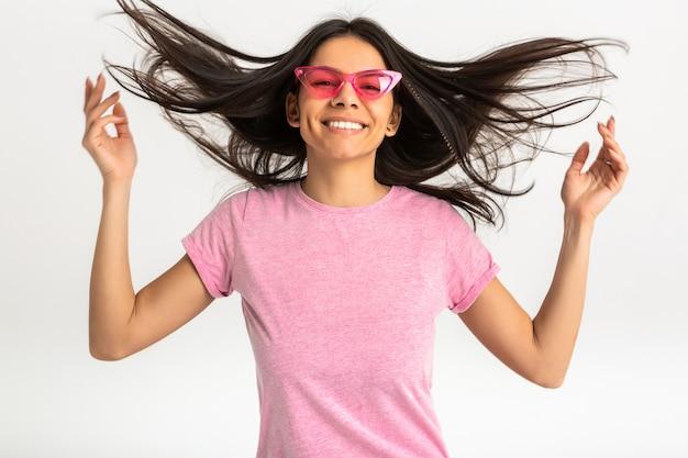 Portrait de femme émotionnelle assez souriante en chemise rose et lunettes de soleil élégantes, dents blanches, posant positif isolé, cheveux longs