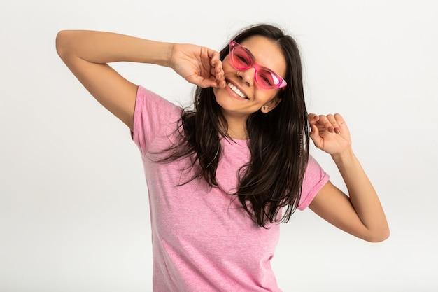 Portrait de femme émotionnelle assez souriante en chemise rose et lunettes de soleil élégantes, dents blanches, pose positive isolée