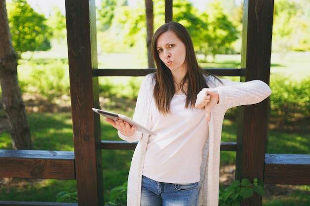Portrait d'une femme émotionnelle triste et bouleversée dans des vêtements décontractés, montrant les pouces vers le bas. fille tenant un ordinateur tablette, lisant de fausses mauvaises nouvelles dans le parc de la ville dans la rue à l'extérieur sur la nature printanière. concept de mode de vie.