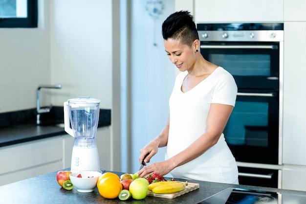 Portrait, de, femme enceinte, dans, cuisine, couper, fruits, sur, planche planche