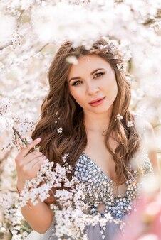 Portrait d'une femme enceinte dans un jardin de printemps en fleurs
