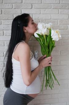 Portrait de la femme enceinte avec des fleurs