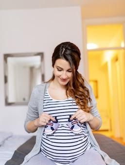 Portrait de femme enceinte heureuse en chemisier à rayures et aux longs cheveux bruns tenant des chaussures de bébé.