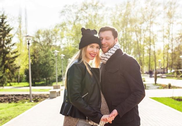 Portrait d'une femme enceinte heureuse et de son mari dans le parc