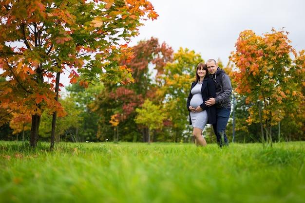 Portrait de femme enceinte heureuse et son mari posant dans le parc d'automne