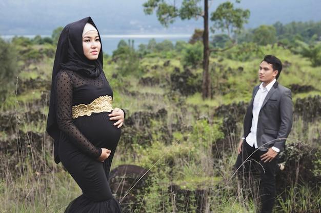 Portrait de femme enceinte portant le hijab et son mari avec paysage nature
