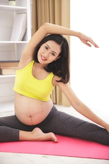 Portrait de femme enceinte saine et heureuse faisant du yoga qui s'étend