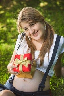 Portrait de femme enceinte souriante posant avec une boîte-cadeau rouge au parc