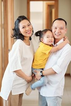 Portrait de femme enceinte touchant son ventre lorsque son mari porte petite fille
