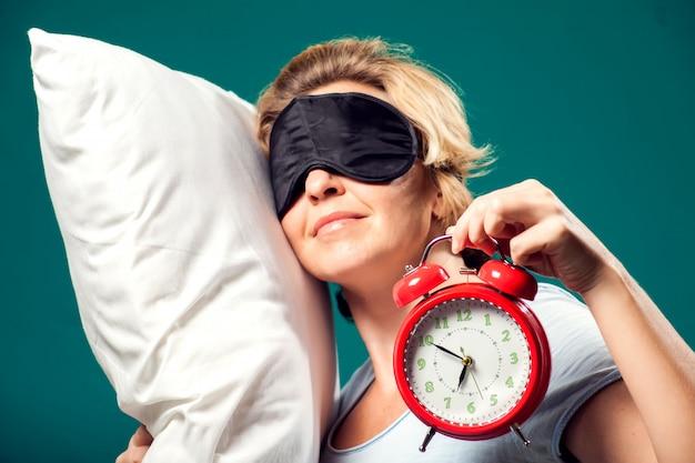Un portrait de femme endormie aux cheveux blonds courts avec un masque de sommeil sur la tête tenant un réveil et un pollow.