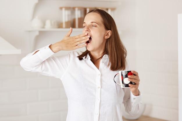 Portrait d'une femme endormie debout dans la cuisine et regardant ailleurs, bâillant, couvrant la bouche avec la main, se réveillant tôt et buvant du thé ou du café chaud dans une tasse.