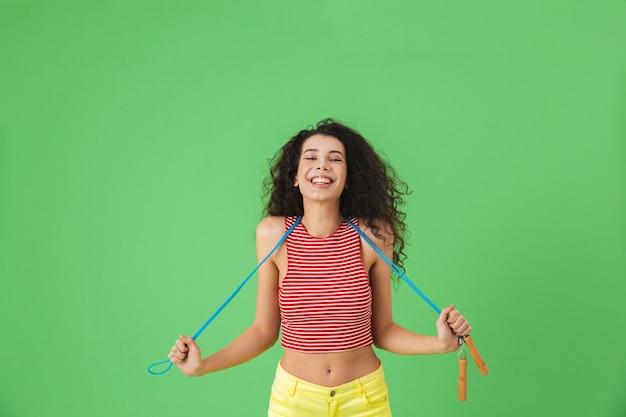 Portrait d'une femme énergique de 20 ans portant des vêtements d'été faisant de l'exercice et faisant des exercices avec une corde à sauter en se tenant debout sur le vert
