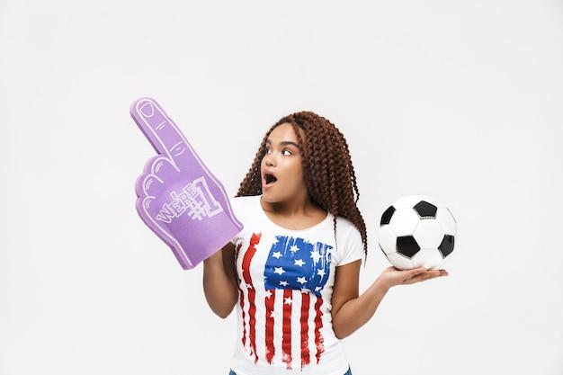 Portrait d'une femme énergique tenant un gant de fan numéro un et un ballon de football en se tenant isolé contre un mur blanc