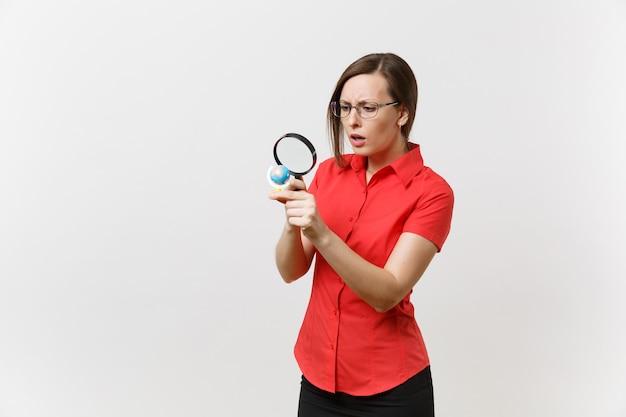 Portrait de femme enseignante d'affaires en chemise rouge tenant et regardant à travers une loupe sur globe isolé sur fond blanc. enseignement de l'éducation dans le concept d'université de lycée. espace de copie.