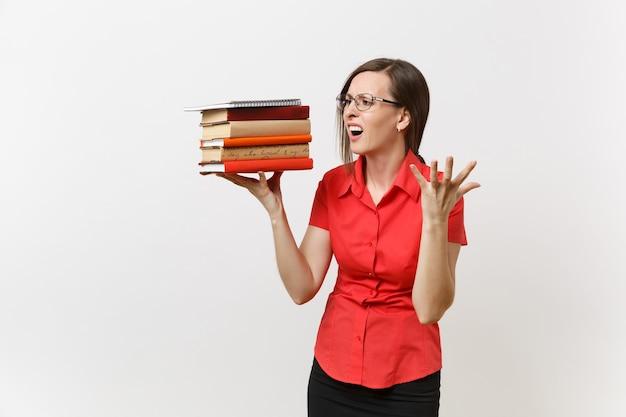 Portrait d'une femme enseignante d'affaires fatiguée, frustrée et bouleversée dans des lunettes de chemise rouge tenant des livres de texte de pile dans les mains isolées sur fond blanc. éducation ou enseignement dans le concept d'université de lycée.