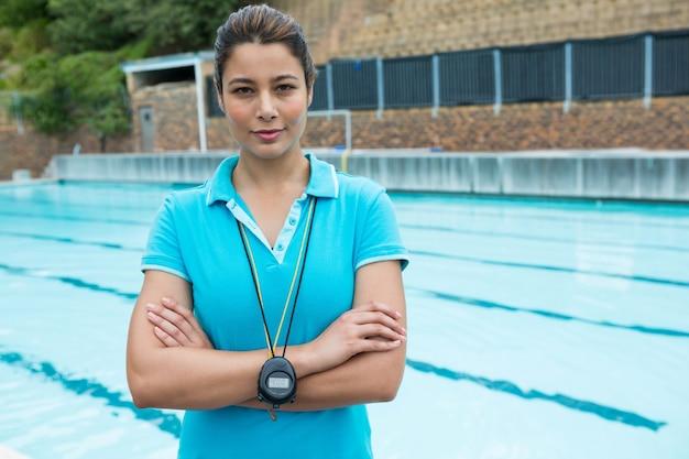Portrait de femme entraîneur debout avec les bras croisés près de la piscine