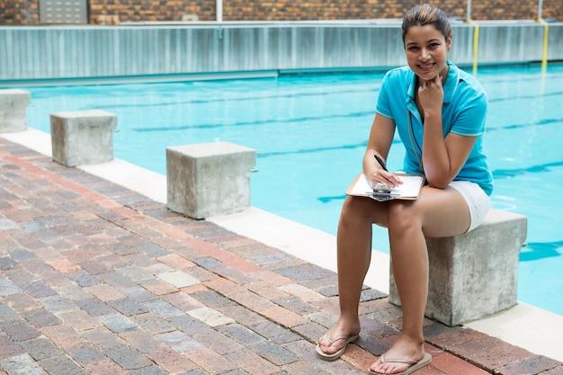Portrait de femme entraîneur souriant assis près de la piscine
