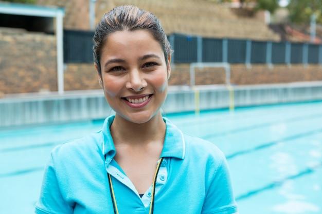 Portrait de femme entraîneur souriant debout près de la piscine