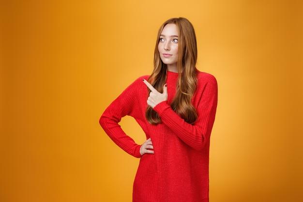 Portrait d'une femme entrepreneur glamour et rousse élégante concevant et dirigeant un nouveau projet pointant vers le coin supérieur gauche comme regardant réfléchi et concentré sur le travail, gérant des affaires sur un mur orange