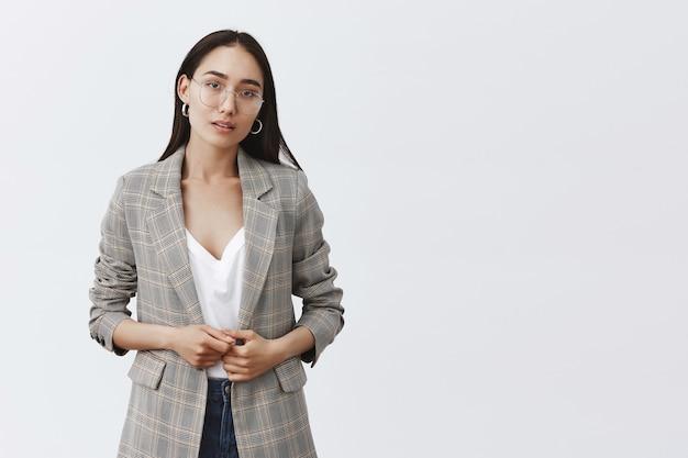 Portrait de femme entrepreneur sérieuse incertaine en veste élégante et lunettes, toucher les doigts et regarder avec doute sur mur gris