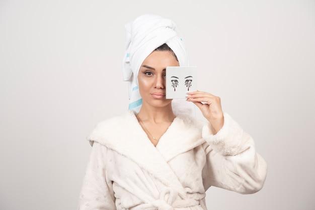 Portrait de femme enveloppée dans une serviette blanche avec palette d'ombres à paupières