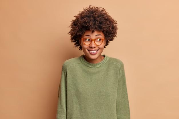 Portrait de femme ethnique assez positive regarde de côté avec un sourire à pleines dents voit quelque chose de gentil porte un pull à manches longues et des lunettes pose en studio contre un mur marron