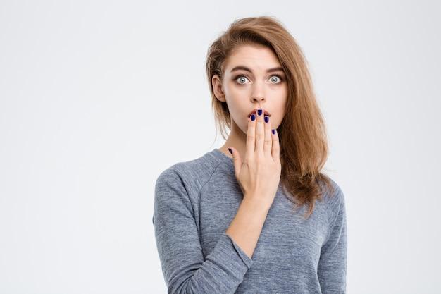 Portrait de femme étonnée couvrant sa bouche avec palm isolé sur fond blanc