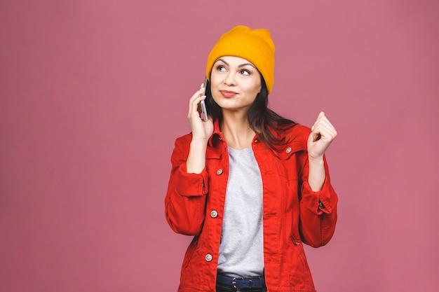 Portrait d'une femme étonnée heureuse dans des vêtements lumineux, parler au téléphone isolé sur le mur rose.