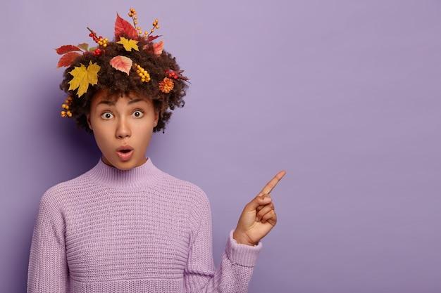 Portrait d'une femme étonnée à la peau sombre pointe sur l'espace de copie, ouvre la bouche, a des feuilles d'automne et des baies de sorbier coincées dans les cheveux, reste sans voix et impressionné, porte un pull violet tricoté.