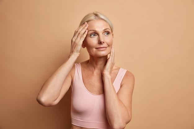 Portrait de femme européenne âgée mature touche doucement le visage a une peau parfaite et regarde pensivement loin bénéficie de son teint doux se soucie de l'apparence satisfaite après la procédure anti-vieillissement