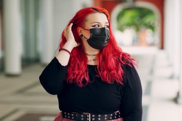 Portrait de femme européenne grande taille en masque facial en plein air rue ville jeune corps aux cheveux rose rouge positi ...