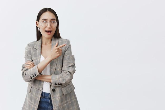Portrait de femme européenne heureuse intriguée à lunettes et veste à la mode, pointant et regardant dans le coin supérieur droit avec une expression étonnée et ravie