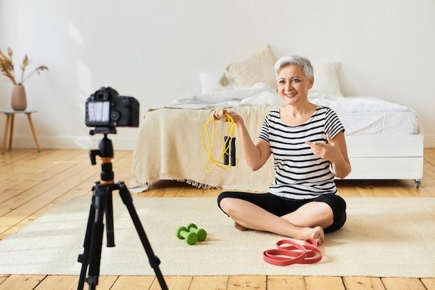 Portrait de femme européenne mature moderne active attrayante retraité formation à l'intérieur, assis sur le sol avec des équipements sportifs, tenant la corde à sauter, parler d'exercices cardio à la caméra