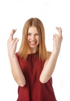 Portrait de femme excitée croisant les doigts contre le blanc.