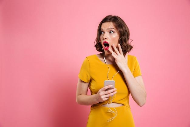Portrait d'une femme excitée dans les écouteurs