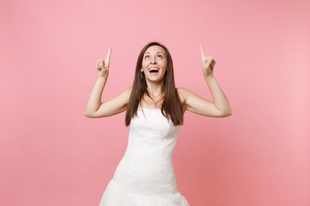 Portrait de femme excitée drôle dans une belle robe blanche debout pointant les doigts vers le haut