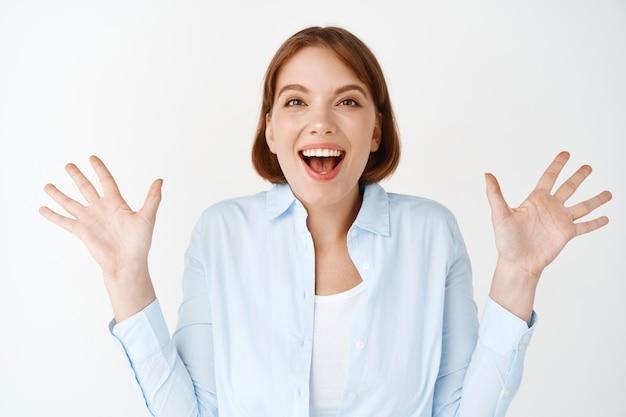 Portrait d'une femme excitée et enthousiaste, écartant les mains sur le côté et criant de joie, gagnant, se sentant heureuse et optimiste, célébrant sur un mur blanc