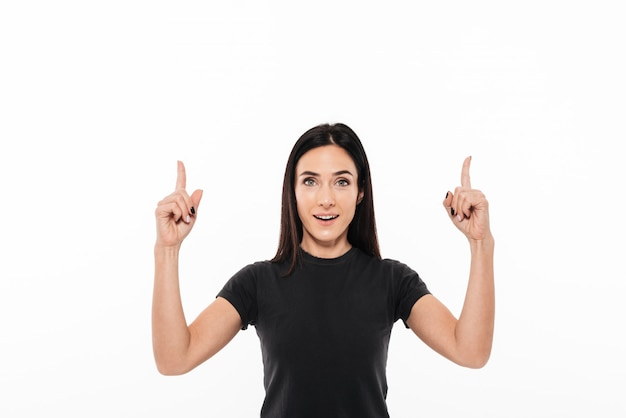 Portrait d'une femme excitée heureuse pointant deux doigts vers le haut