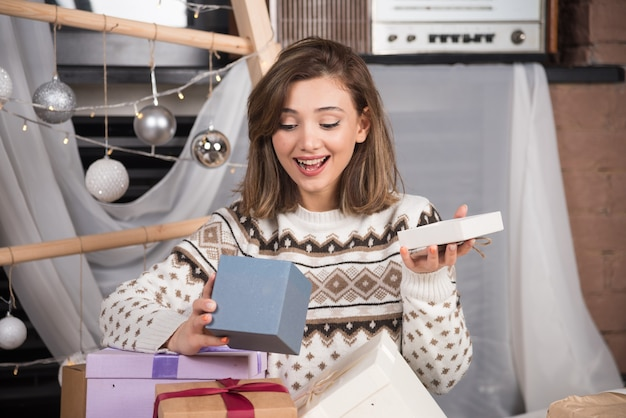 Portrait d'une femme excitée ouvrant le cadeau de noël.