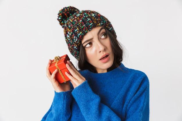Portrait de femme excitée portant un chapeau d'hiver tenant la boîte présente en position debout, isolé sur blanc